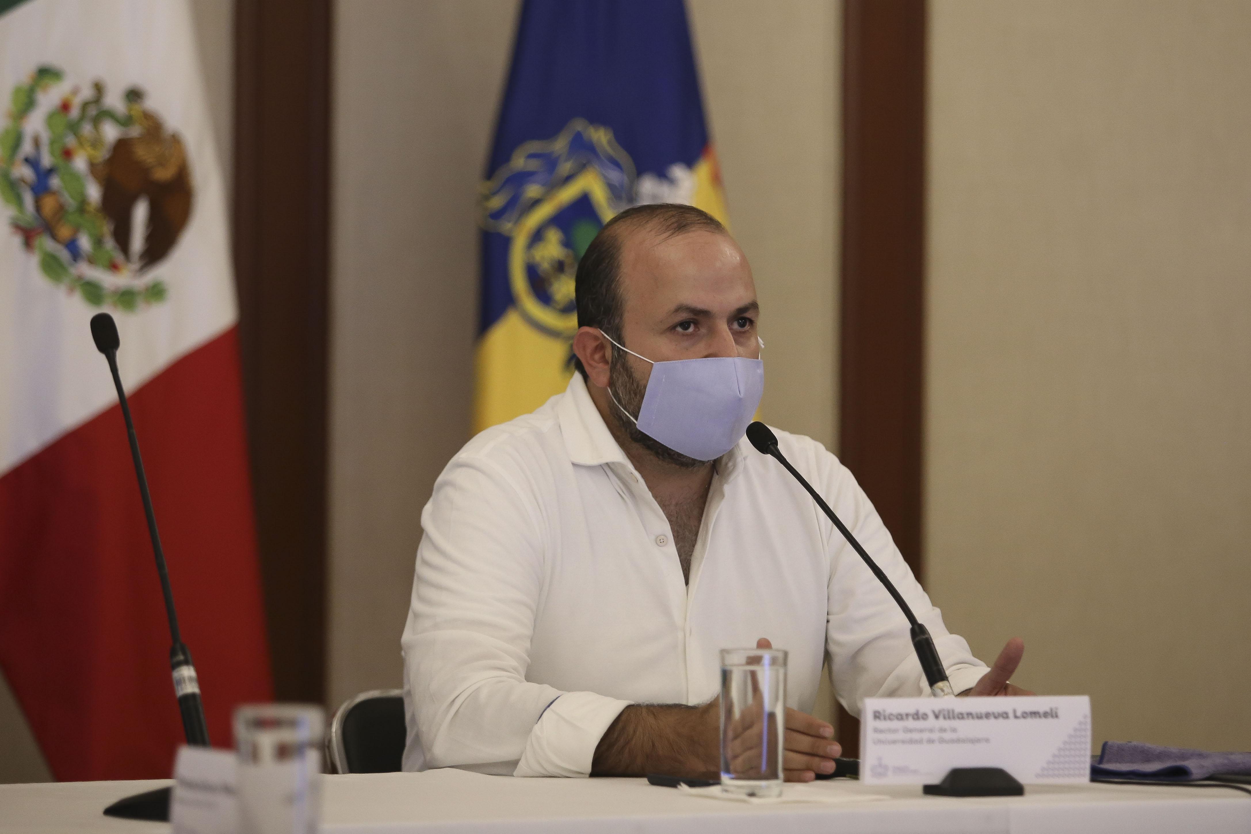 Rector General al micrófono con cubrebocas en rueda de prensa virtual en Casa Jalisco