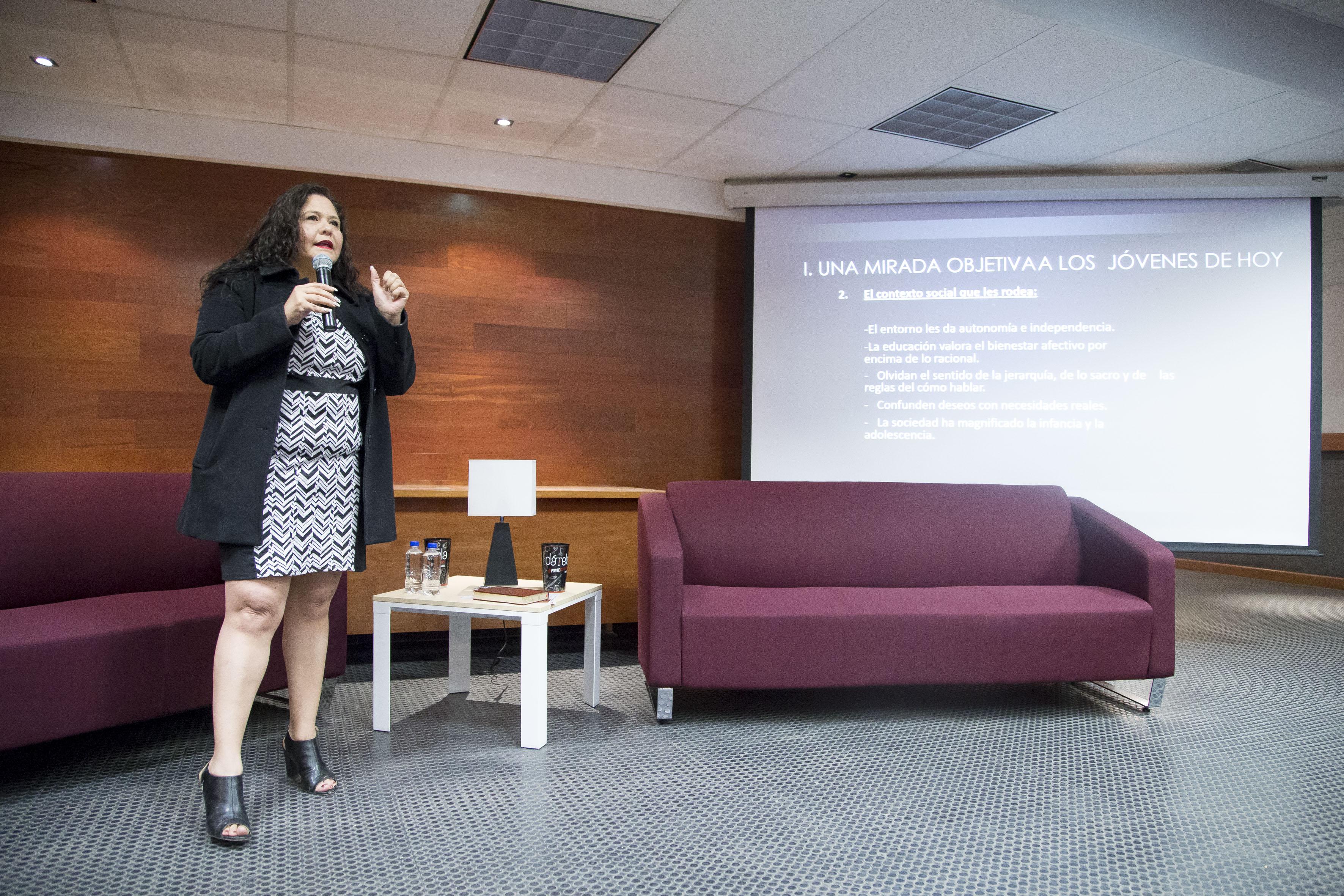 Mtra Caty Pérez dictando conferencia. A la vista el escenario del auditorio