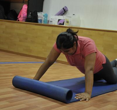 Estudiante sobre un tapete ejecutando una postura de yoga