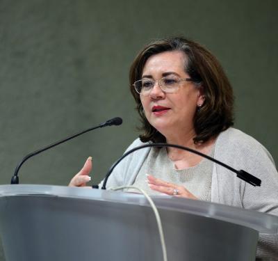 Dra Ana Mercado haciendo uso de la voz en podium
