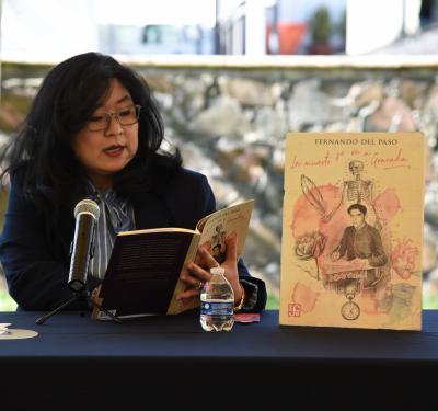 Coordinadora de Extensión leyendo en voz alta en la mesa de lectura con micrófono