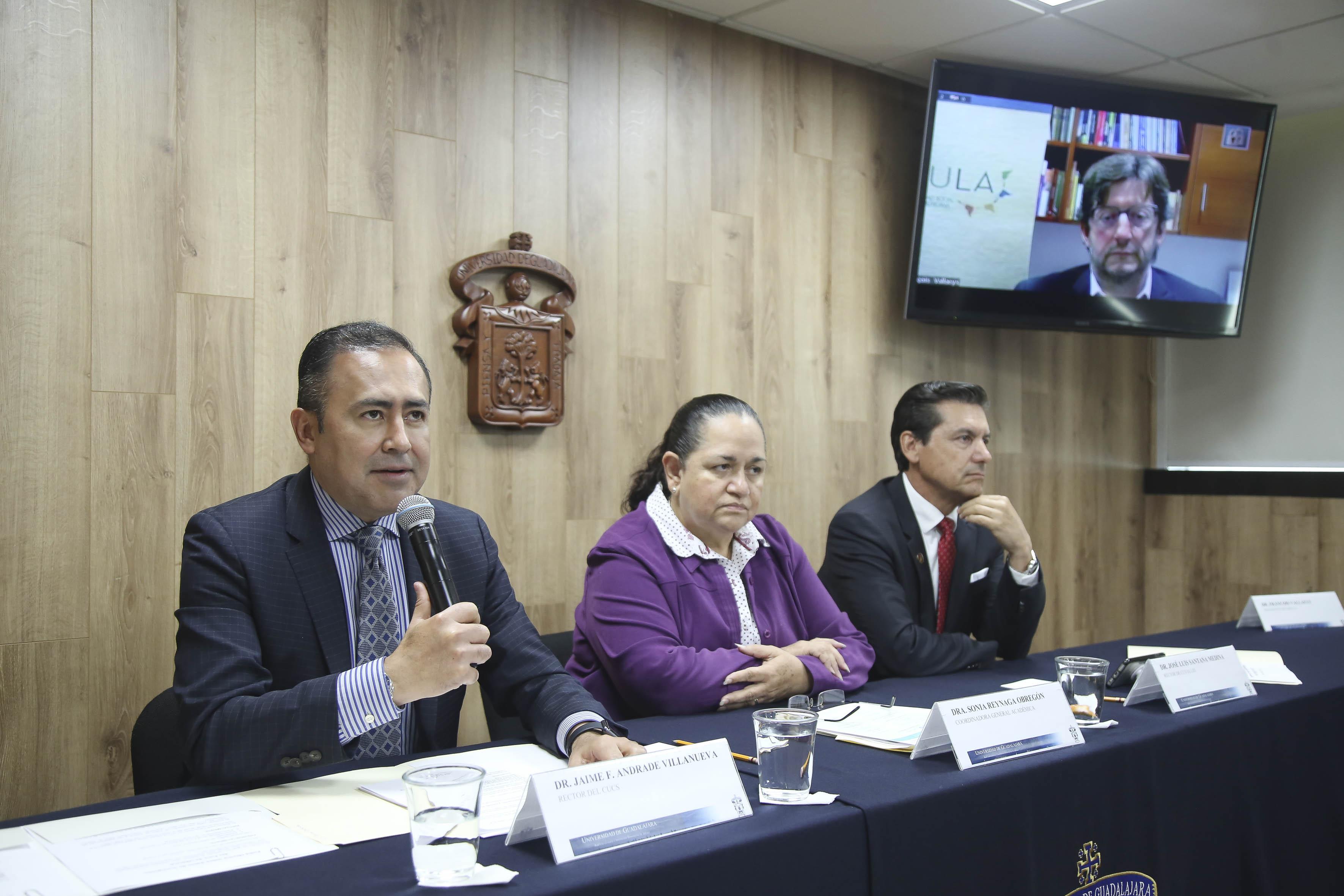 Rector CUCS al micrófono en Rueda de Prensa junto con los miembros del presídium