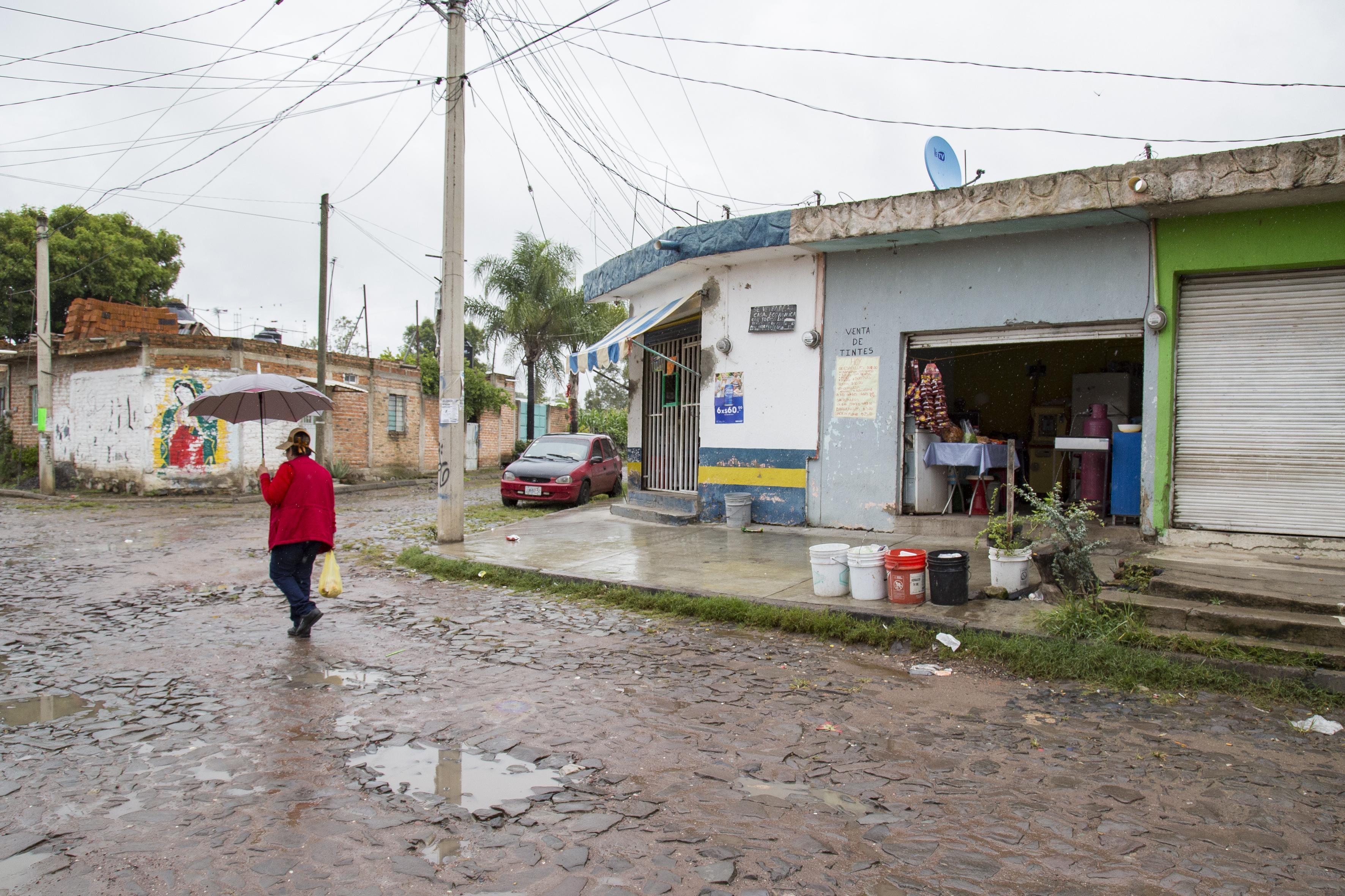 Señora caminando bajo la lluvia en una colonia de El Salto