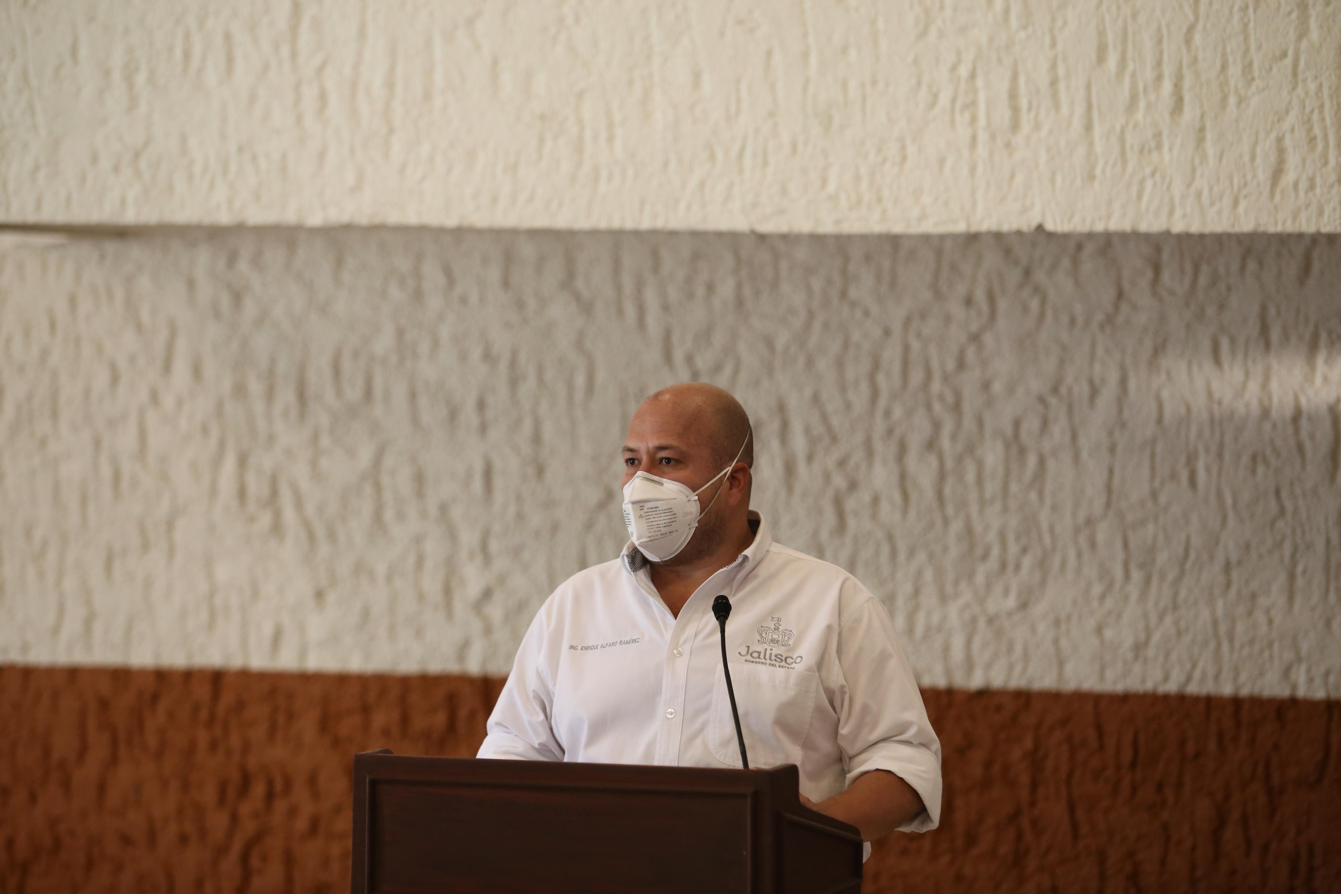 Gobernador de Jalisco al micrófono en el pódium durante rueda de prensa virtual