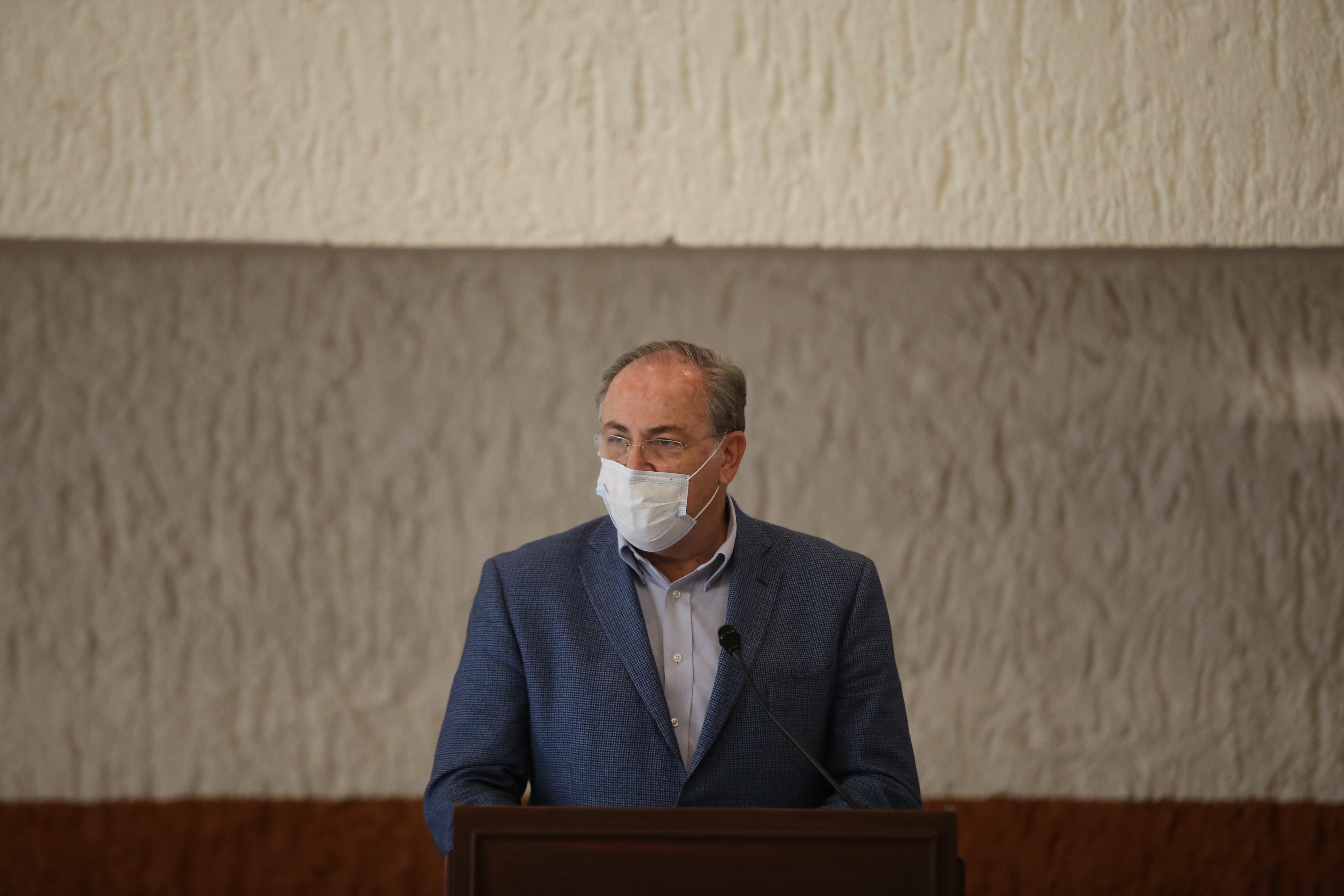 Secretario de Salud al micrófono en el pódium durante rueda de prensa virtual