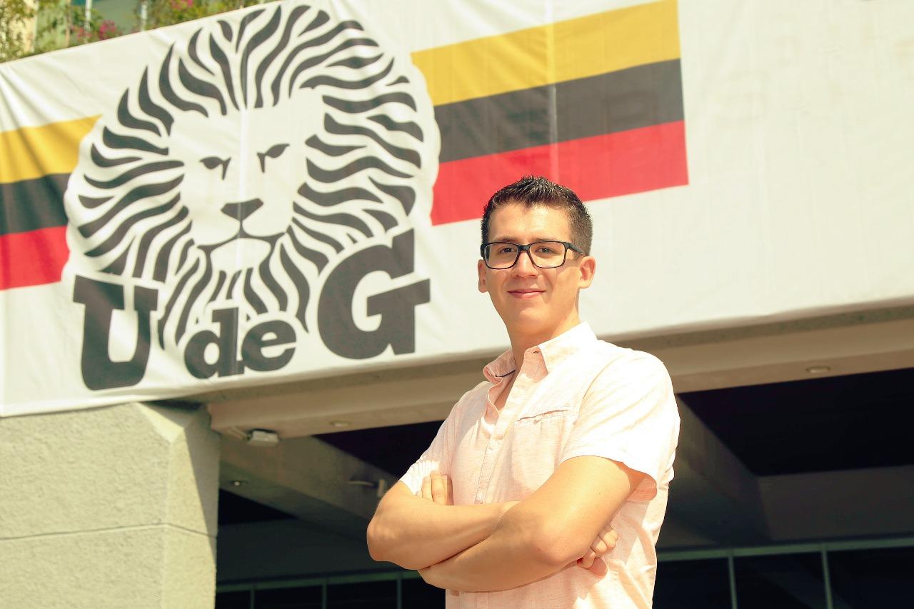 Alumno posa en la explanada del Edificio de Rectoría General, a sus espaldas el escudo de la UdeG