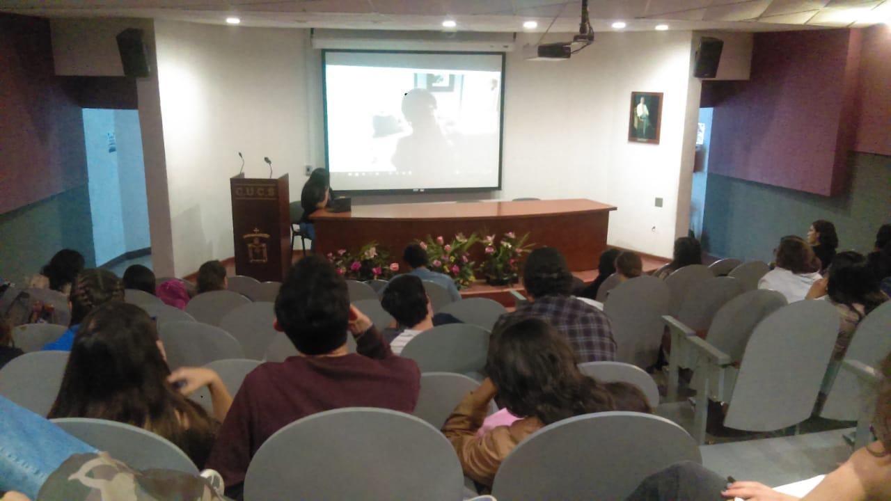 En la pantalla, la Dra. Gloria González. En el presídium, la Mtra. Verónica Rubí Beltrán transmitiendo la conferencia