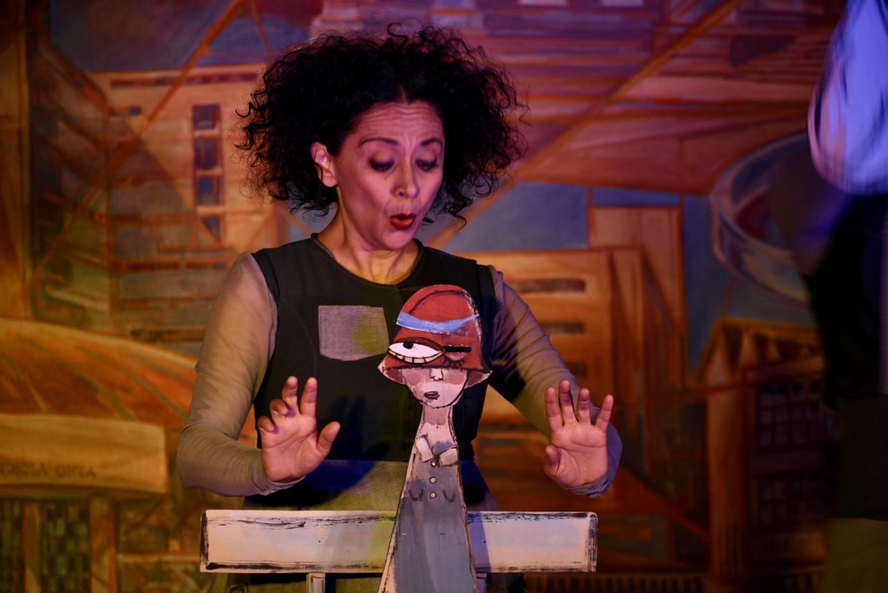 Actriz y marioneta actuando durante la obra de teatro