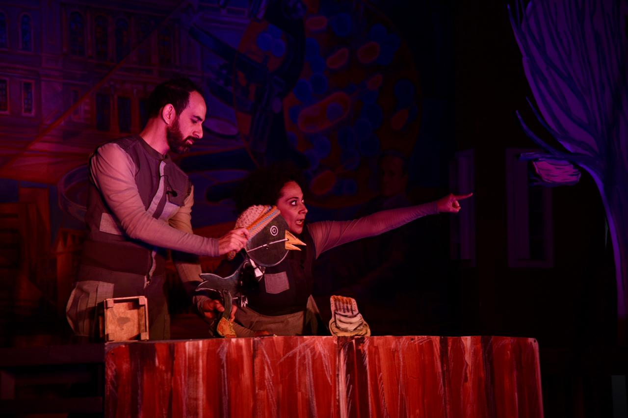 Actores interactuando con marionetas durante la obra de teatro